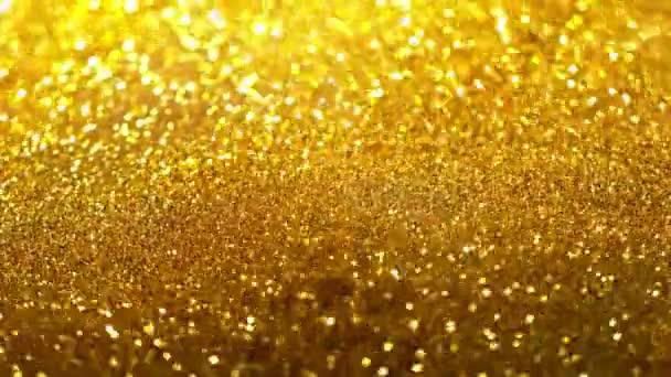 Super pomalý pohyb třpytivých zlatých částic na černém pozadí. Mělká hloubka soustředění. Natočeno na vysokorychlostní kameře, 1000 fps.