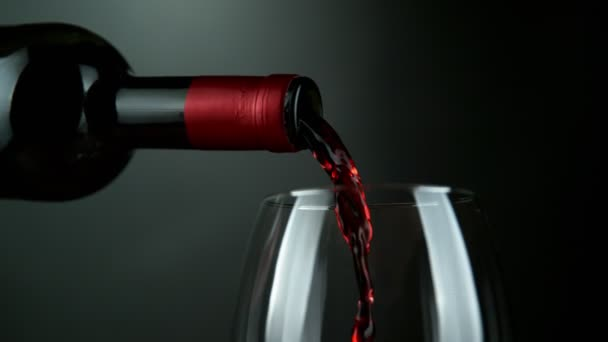 Super slow motion of pouring red wine into glass in detail. Filmed on high speed cinema camera, 1000 fps