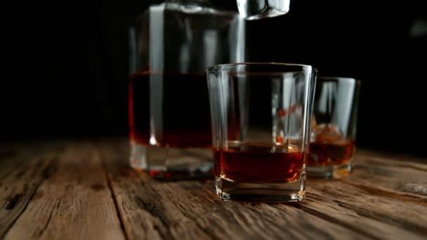 Super-Zeitlupe fallender Eiswürfel in Whiskey-Drink mit Kamerafahrt. Gefilmt mit High-Speed-Kinokamera, 1000 fps.