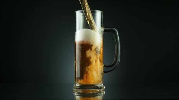 Super zpomalený pohyb nalití pivního nápoje do skla, umístěného na černém pozadí. Natočeno na vysokorychlostní kameře, 1000 fps.