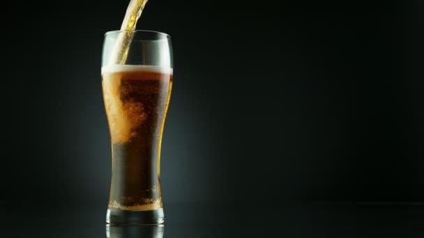 Super Zeitlupe des Einfüllens von Biergetränken in Glas, platziert auf schwarzem Hintergrund. Gefilmt mit High-Speed-Kinokamera, 1000 fps.