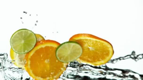 Super zpomalený pohyb citronu, limetky a pomerančových plátků s postříkanou vodou. Natočeno na vysokorychlostní kameře, 1000 fps.