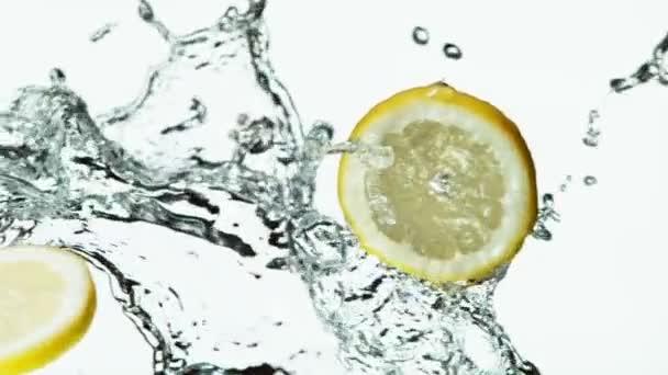 Super pomalý pohyb citrónových plátků s vodou stříkající na bílou. Natočeno na vysokorychlostní kameře, 1000 fps.