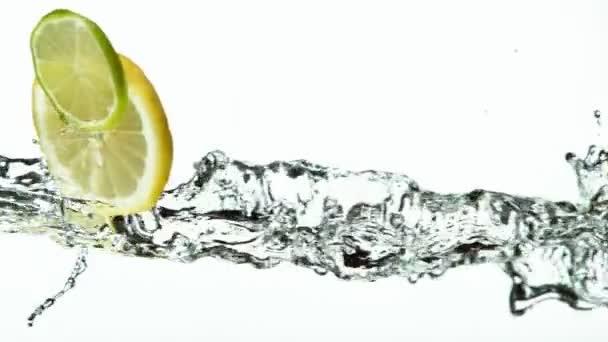 Super pomalý pohyb vápna a citronu plátky s vodou stříkající na bílém pozadí. Natočeno na vysokorychlostní kameře, 1000 fps.
