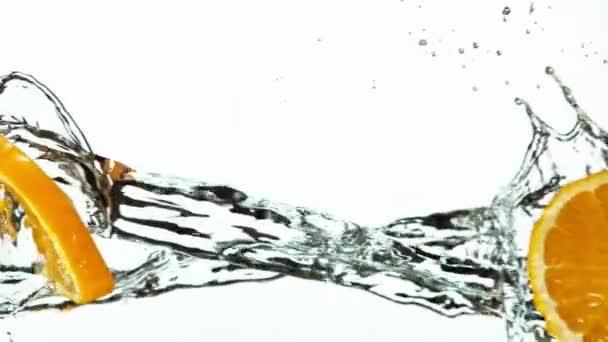 Super pomalý pohyb oranžových plátků s vodou stříkající na bílém pozadí. Natočeno na vysokorychlostní kameře, 1000 fps.