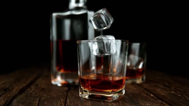 Super zpomalený pohyb padající kostky ledu do whiskey drinku, pohyb kamery. Natočeno na vysokorychlostní kameře, 1000fps