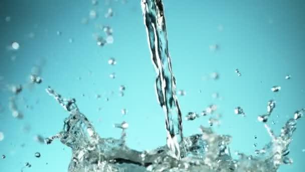 Super zpomalený pohyb stříkající vody na modré pozadí. Natočeno na vysokorychlostní kameře, 1000fps.