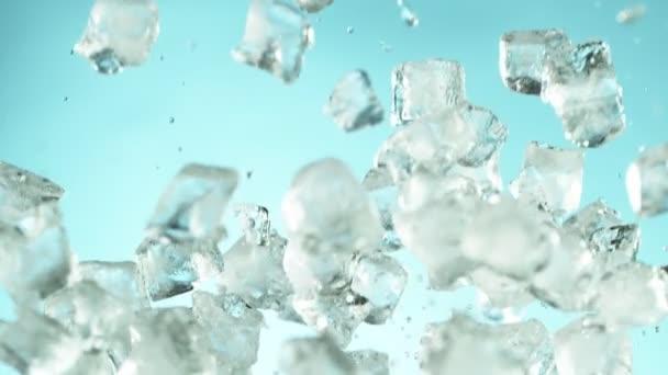 Super-Zeitlupe fallender Eiswürfel getrennt auf blauem Hintergrund. Gefilmt mit High-Speed-Kinokamera, 1000 fps.