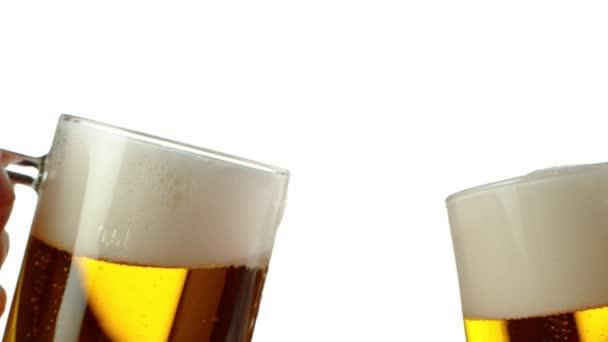 Super zpomalený pohyb dvou sklenic piva narážejících do sebe, koncepce na zdraví. Natočeno na vysokorychlostní kameře, 1000 fps.