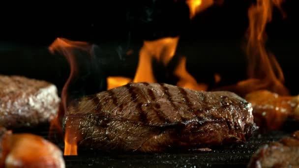 Super zpomalený pohyb hovězího steaku na grilu s ohněm, izolovaný na černém pozadí. Natočeno na vysokorychlostní kameře, 1000 fps
