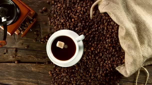 Super zpomalený pohyb padající cukrové třtiny do šálku kávy. Natočeno na vysokorychlostní kameře, 1000 fps.