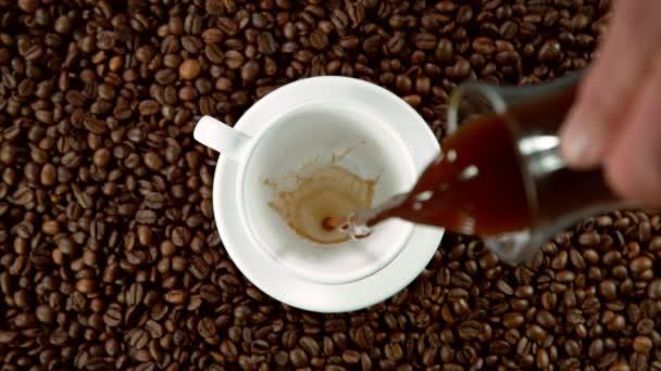 Super zpomalený pohyb nalévání kávy do šálku, vysoký úhel pohledu. Natočeno na vysokorychlostní kameře, 1000 fps.