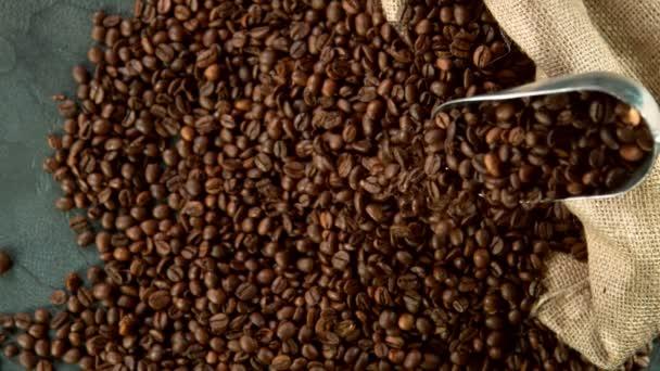 Super zpomalený pohyb padajících kávových zrn z lžíce. Natočeno na vysokorychlostní kameře, 1000 fps.