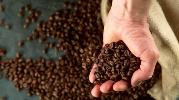 Super zpomalený pohyb mužských rukou nalévajících kávová zrnka. Natočeno na vysokorychlostní kameře, 1000 fps.