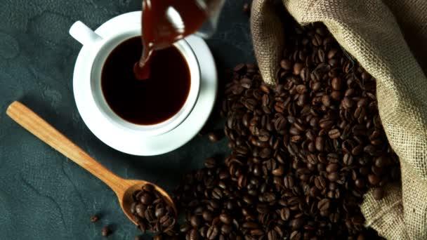 Super zpomalený pohyb nalévání kávy do šálku, vysoký úhel pohledu. Natočeno na vysokorychlostní kameře, 1000fps.