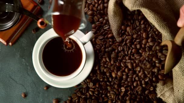 Szuper lassított felvétel a kávé pohárba öntéséről, nagy látószögből. Filmre véve nagy sebességű mozi kamera, 1000fps.