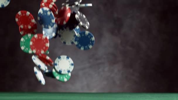 Super pomalý pohyb padajících pokerových žetonů s šedým pozadím. Natočeno na vysokorychlostní kameře, 1000fps.