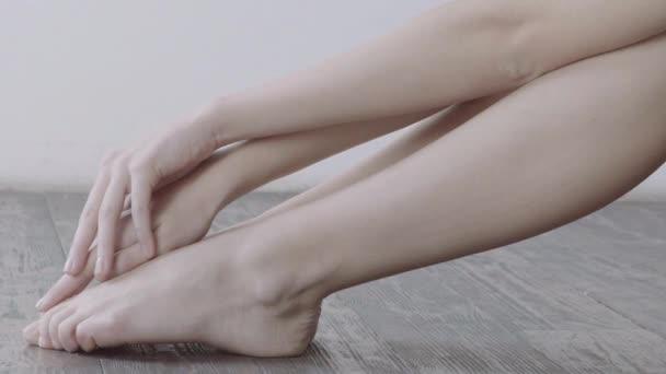 Dívka opatrně dotýkat se jí nohy sedící na dřevěné podlaze s bílou zdí na pozadí