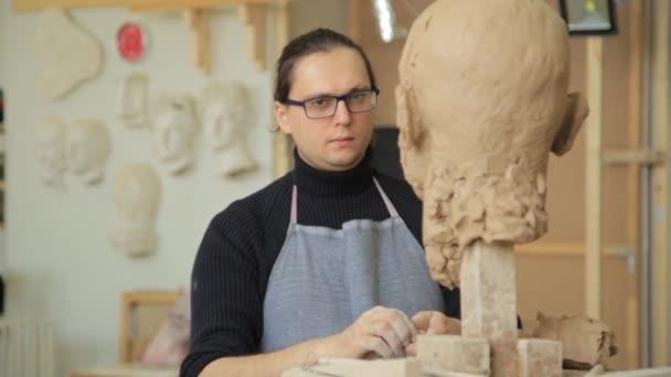 Sochař, modelování sochy úprava obličeje detaily hlavy z hlíny.