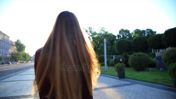 Šťastná dívka s dlouhými vlasy, baví venkovní ve městě při východu slunce. Krása žena točí, skákání a směje se. Svoboda