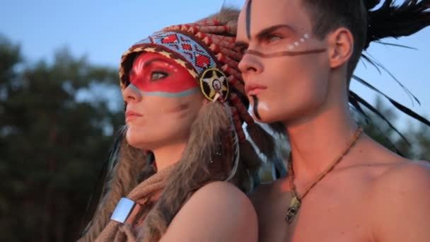 schöne indianische Ureinwohner Mann und Frau in traditioneller Kleidung am Meeresstrand bei Sonnenuntergang