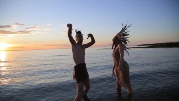 Indianische Indianer suchen schöne Mann und Frau tanzen am Meeresstrand mit der Sonne bei Sonnenuntergang