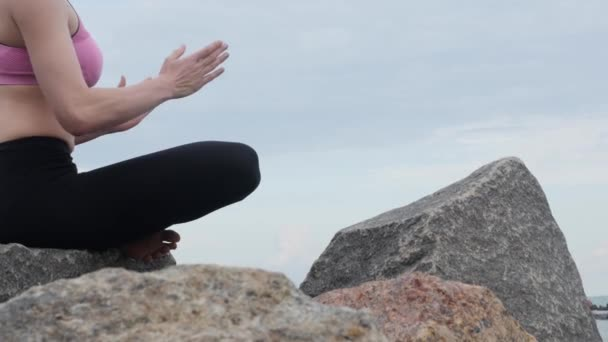 Girl practices yoga fitness exercise near the ocean beach sitting on the stone in lotus pose