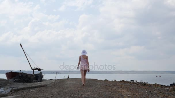 Tourist woman in beautiful dress walking to horizon. Travel experience at sunset, girl enjoying relaxed lifestyle on summer vacation.