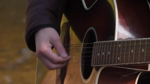 Hezký asijský mladík hrál na kytaru na pobřeží Lesní řeky za úsvitu. Dawn misty mlha na pozadí