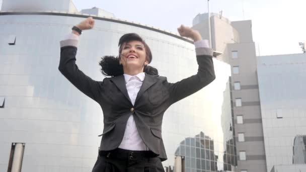 Happy kavkazské obchodní žena skákání a slaví před kancelářská budova.
