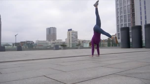 junge attraktive Frau macht Akrobatik mit Stadtbild im Hintergrund