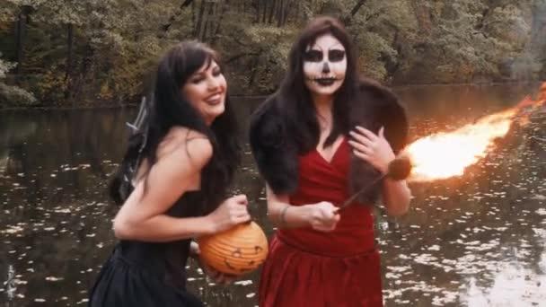Halloween Mädchen Jugendliche in schwarzen und roten Hexenkleid Spaß im Waldpark mit traditionellen Herbstferien Symbol orange gruseligen Kürbis im freien