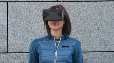 Woman using finger to touch on imaginary panel viewing on VR device outdoors. Augmented virtual reality concept