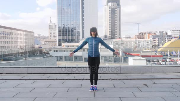 Woman practicing yoga fitness exercise at city background with office buildings wearing vr virtual reality headset
