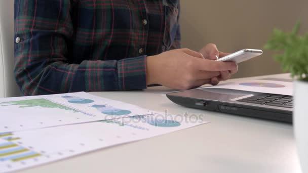 Detail z mladých obchodních žena pracující v kanceláři interiéru na pc držte smartphone a díval se na obrazovky s diagramy. Úřadu osoba, která používá mobilní telefon a notebook