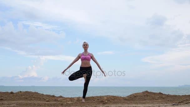 Mädchen übt Yoga-Fitnessübungen am Strand in Baumpose