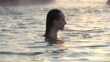 Geothermal spa. Woman relaxing in hot spring pool outdoors