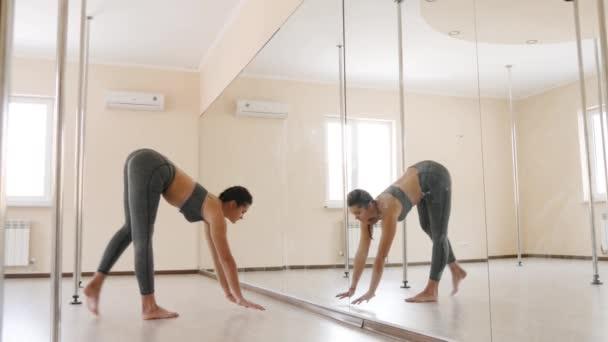 Fitness női csinál nyújtó edzés akrobatika közelében a tükör. Fiatal nő gyakorlása fedett