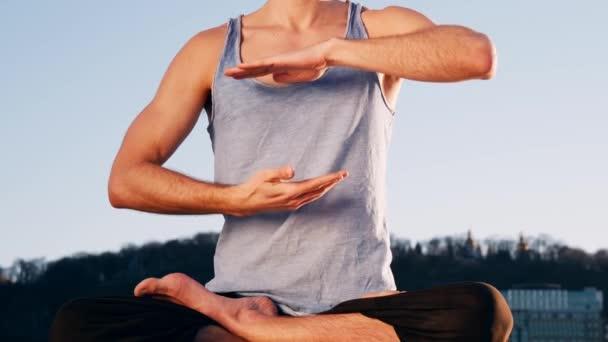 junger kaukasischer Mann entspannt sich durch Yoga-Fitness-Übungen am Strand in der Nähe des ruhigen Flusses mit Stadt im Hintergrund