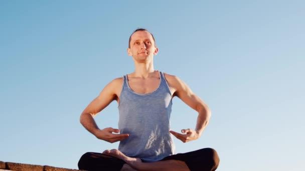 Kaukázusi fiatalember pihentető gyakorló jóga fitness edzés a tengerparton, nyugodt város háttér-folyó közelében