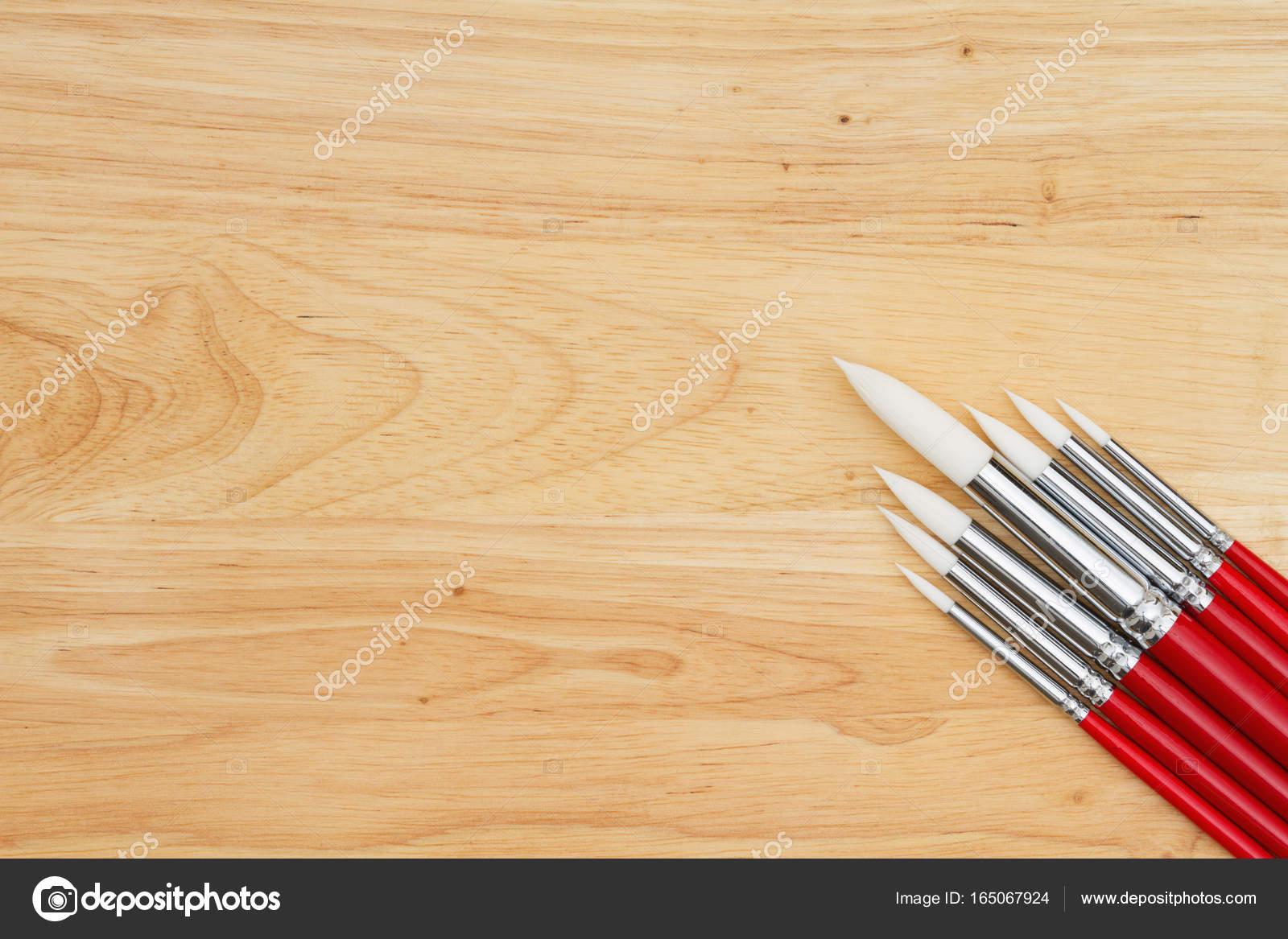 Jeu de brosses de peinture rouge sur le bureau bois u2014 photographie