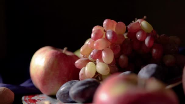 Still life with fruit and red wine. Grapes, apples, pear, plums, nuts and blue drapery