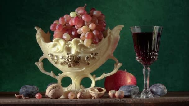 Zátiší s ručně vyráběným hliněným džbánem, hrozny ve váze, švestkami, jablky, ořechy, hruškami a sklenicí vína