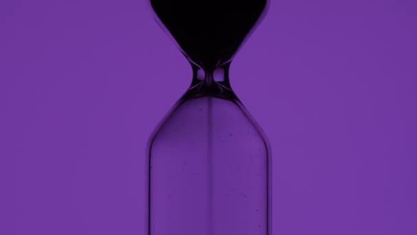 Az idő múlása. Homokóra színes háttérrel közelkép
