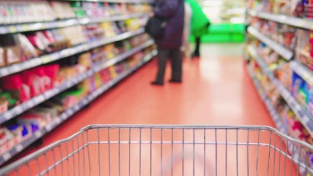Kovový jídelní vozík se pohybuje a stojí v supermarketu, mezi regály se zbožím