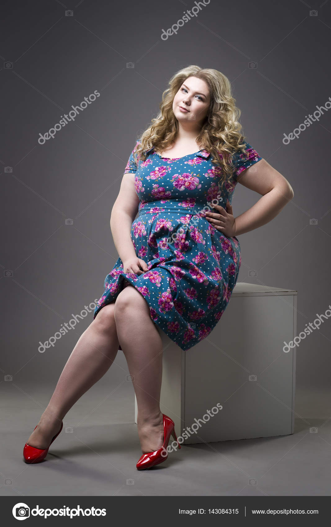 Young beautiful happy blonde plus size model in dress and ...