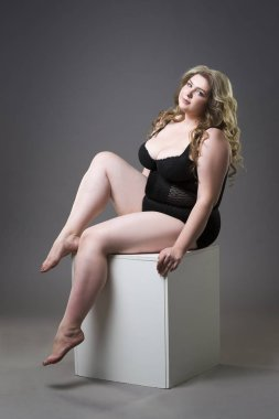 Young beautiful blonde plus size model in shapewear, xxl woman in slimming underwear on gray studio background