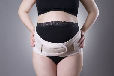 Pregnant woman in black underwear with orthopedic support belt, pregnancy bandage