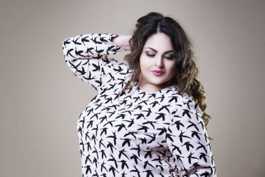 Plus size fashion model in casual clothes, fat woman on studio background, overweight female body