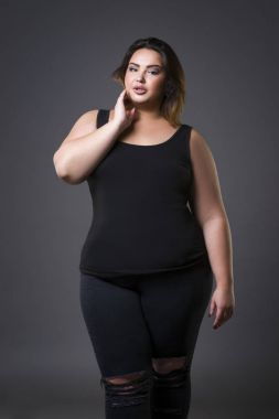 Plus size fashion model in casual clothes, fat woman on gray background, overweight female body